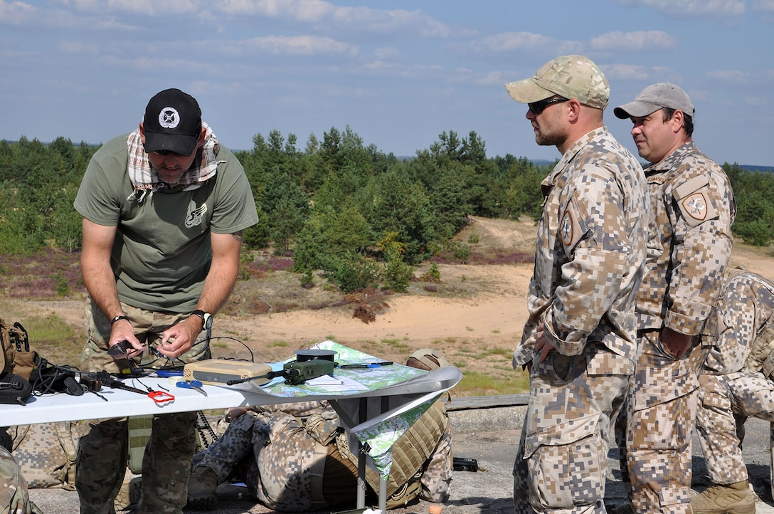 Master Sgt. Chuck Barth, a Joint Terminal Attack Controller with the Combat Readiness Training Center from Alpena, Mich., trains Sgt. Juris Salajves and Cpl. Andries Simanis, both with the Latvian military, on how to set up an antenna to establish communications during a range training exercise Aug. 24 at Adazi Range in Latvia. JTAC's from two Air National Guard units are training with the Latvians in ground maneuvers calling for close air support using A-10 Thunderbolt IIs with the 442d Fighter Wing from Whiteman Air Force Base, Mo. U.S. forces are training with NATO allies as part of Operation Atlantic Resolve. (U.S. Air Force photo by Capt. Denise Haeussler