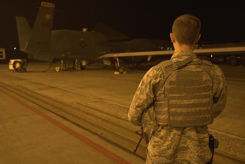 U.S. Air Force Airman 1st Class Caleb Kenley, 35th Security Forces Squadron installation entry controller, oversees the security of a RQ-4 Global Hawk at Misawa Air Base, Japan, Aug. 19, 2015. During the RQ-4's six-month rotation to Misawa, direct safety and security is provided to ensure the aircraft is protected and ready to perform its mission. (U.S. Air Force photo by Senior Airman Jose L. Hernandez-Domitilo/Released)
