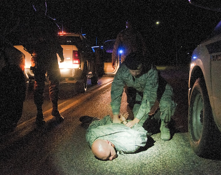 Senior Airman Zachary Downey, 90th Security Forces Squadron Delta Flight, pins down and handcuffs Technical Sgt. Andreas Niemetschek, 90th SFS Delta Flight chief, during a nighttime training exercise Aug. 6, 2015, on F.E. Warren Air Force Base, Wyo. Every shift, day and night, 90th SFS defenders undergo at least one training exercise to keep their law enforcement skills sharp. Niemetschek simulated a gate runner and led Delta Flight on a car chase through the base before being surrounded and subdued. Niemetschek was not apprehended except for exercise purposes only. (U.S. Air Force photo by Senior Airman Jason Wiese/Released)