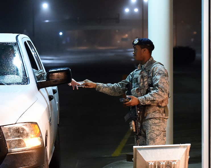Airman 1st Class Bradley Hill, 90th Security Forces Squadron, checks the ID card of drivers at the front gate of F.E. Warren Air Force Base, Wyo., in the early-morning hours of April 8, 2015. Airmen work as entry controllers for 12-hour shifts starting the evening before at 6 p.m. (U.S. Air Force photo by R.J. Oriez)