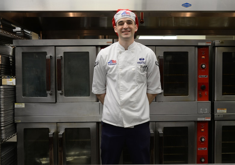 U.S. Air Force Airman 1st Class Jeremy P. Hnatiuk, a 354th Force Support Squadron shift leader, takes a break to smile in front of the ovens in the Two Seasons Dining Facility, Aug. 27, 2015, at Eielson Air Force Base, Alaska. Hnatiuk said his favorite part of the job is cooking, which is something he has always loved to do. (U.S. Air Force photo by Airman 1st Class Cassandra Whitman/Released)