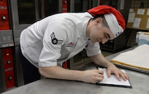 U.S. Air Force Airman 1st Class Jeremy P. Hnatiuk, a 354th Force Support Squadron shift leader, signs a food log in the kitchen of the Two Seasons Dining Facility, Aug. 27, 2015, at Eielson Air Force Base, Alaska. This paperwork tells Hnatiuk what he and other cooks need to prepare for each days meals. (U.S. Air Force photo by Airman 1st Class Cassandra Whitman/Released)