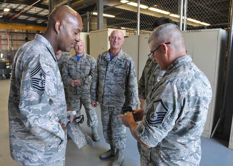 AFRC Command Chief Cameron B. Kirksey checks out photos with Master Sgt. David L. Wallis, an engine mechanic with the 507th Aircraft Maintenance Squadron during a three-day tour of the 507th Air Refueling Wing August 9, 2015, at Tinker Air Force Base, Okla. Kirksey has visited more than 20 Reserve units during his tenure as command chief. (U.S. Air Force photo by Staff Sgt. Lauren Gleason)