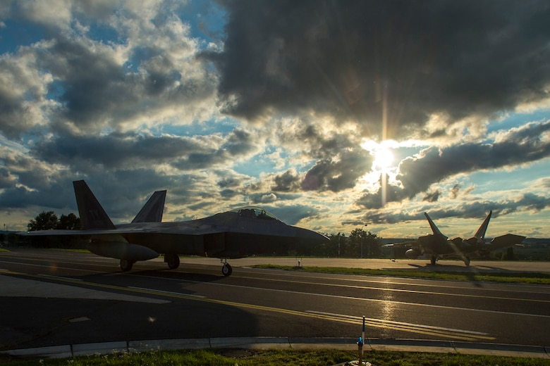 Two F-22 Raptor fighter aircraft assigned to the 95th Fighter Squadron at Tyndall Air Force Base, Fla., taxi to hardened aircraft shelters at Spangdahlem Air Base, Germany, Aug. 28, 2015.The U.S. Air Force deployed four F-22s, one C-17 Globemaster III and more than 50 Airmen to Spangdahlem in support of the first F-22 European training deployment. The inaugural F-22 training deployment to Europe is funded by the European Reassurance Initiative, a $1 billion pledge announced by President Obama in March 2014.(U.S. Air Force photo by Airman 1st Class Luke Kitterman/Released)