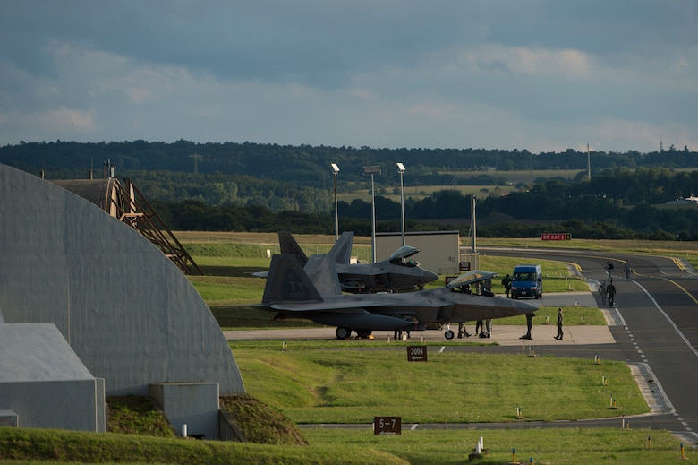 Members of the 95th Fighter Squadron from Tyndall Air Force Base, Fla., marshal two U.S. Air Force F-22 Raptor fighter aircraft near hardened aircraft shelters, Aug. 28, 2015, on Spangdahlem Air Base, Germany. The 95th FS deployed to Spangdahlem as part of the European Reassurance Initiative, which is intended to increase the capability, readiness and responsiveness of NATO forces in part by funding rotational force presence in Eastern Europe. This training deployment is also part of ensuring the 5th generation fighters can deploy to European bases and other NATO installations. (U.S. Air Force photo by Staff Sgt. Christopher Ruano/Released)
