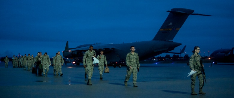 Airmen from the 95th Fighter Squadron depart from a U.S. Air Force C-17 Globemaster III on the flightline at Spangdahlem Air Base, Germany, Aug. 28, 2015. The Airmen are here to support the first ever F-22 Raptor European training deployment. This deployment is part of the European Reassurance Initiative, which is intended to increase the capability, readiness and responsiveness of NATO forces in part by funding rotational force presence in Eastern Europe. (U.S. Air Force photo by Senior Airman Rusty Frank/Released)