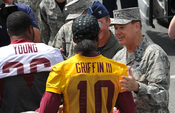 Air Force District of Washington Commander Maj. Gen. Darryl Burke greets Washington Redskins quarterback Robert Griffin III just before the Washington Redskins conduct a walkthrough practice at the fitness center's field, Joint Base Andrews, Md. on Aug. 28, 2015. The Redskins spent time meeting with Airmen, Sailors and Marines, family members and local school children and their chaperones to show their appreciation to the military community. The Redskins conducted the practice and signed autographs as part of their Redskins Salute effort. (U.S. Air Force photo/James E. Lotz)