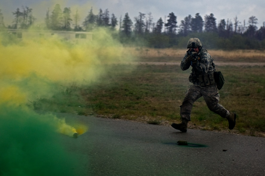 U.S. Air Force Senior Airman Nicholas Collins, with the 121st Security Forces Squadron, runs for cover during a training exercise Aug. 19, 2015 at Camp Grayling Joint Maneuver Training Center, Mich. Airmen with the 121st SFS spent three days in a simulated deployed environment at Camp Grayling as a part of their annual training. (U.S. Air National Guard photo by Airman Ashley Williams/Released)