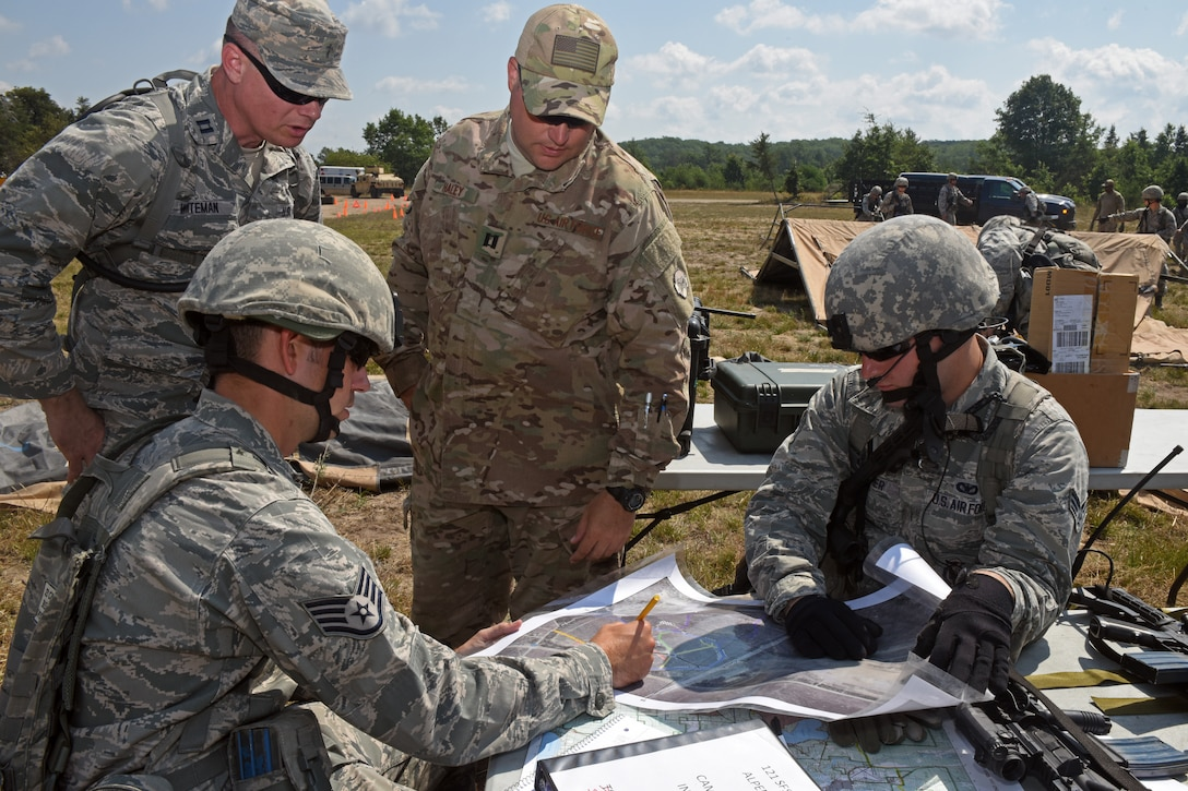 U.S. Airmen with the 121st Security Forces Squadron plan routes of approach to the village during a training exercise Aug. 17, 2015 at Camp Grayling Joint Maneuver Training Center, Mich. The 121st SFS Airmen spent three days at Camp Grayling in a simulated deployed environment as a part of their annual training. (U.S. Air National Guard photo by Airman Ashley Williams/Released)