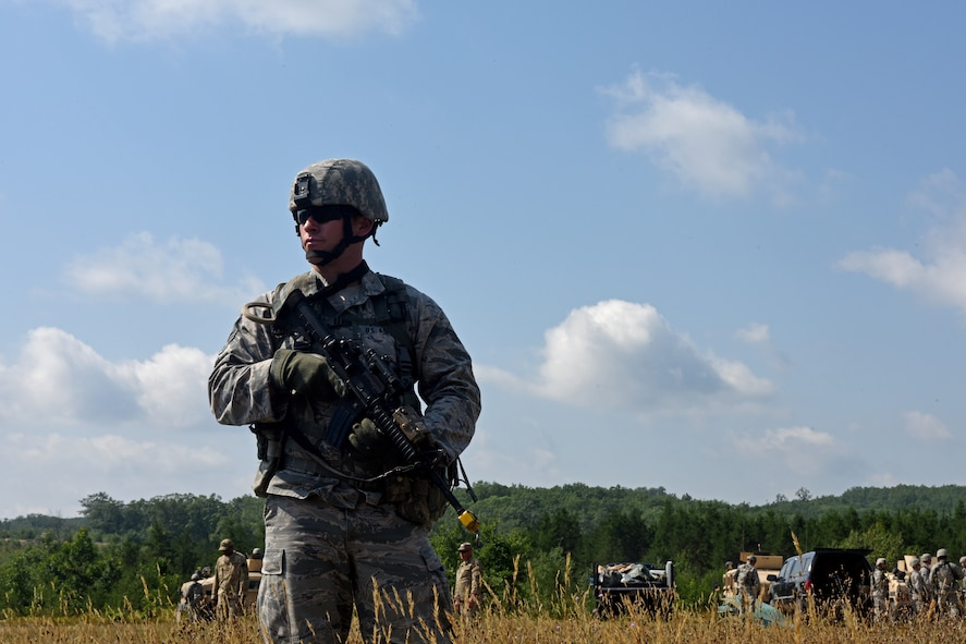 U.S. Air Force Senior Airman Cody Martin, with the 121st Security Forces Squadron, establishes security while 121st SFS Airmen set-up a Forward Operating Base during a training exercise Aug. 17, 2015 at Camp Grayling Joint Maneuver Training Center, Mich. The Airmen spent three days in a simulated deployed environment as a part of their annual training. (U.S. Air National Guard photo by Airman Ashley Williams/Released)