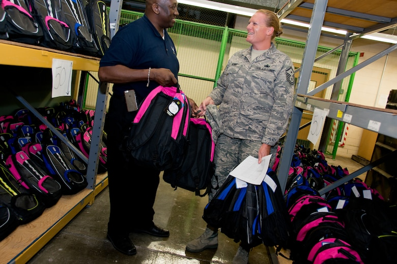 Mark Gillard, Airman and Family Readiness Specialist, helps Master Sgt. Tori Kenny, 102nd Logistics Readiness Squadron First Sergeant, with carrying backpacks filled with school supplies for 102 IW military children. The Otis Civilian Advisory Council donated more than 350 backpacks to the wing. (Massachusetts Air National Guard photo by Tech. Sgt. Kerri Spero)