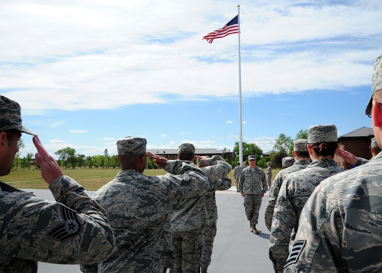 Airmen from the 319th Air Base Wing Staff Agencies salute the flag during a formal retreat practice August 19, 2015, on Grand Forks Air Force Base, North Dakota. Airmen are required to salute the flag while it is raised or lowered. (U.S. Air Force photo by Airman 1st Class Ryan Sparks/Released)