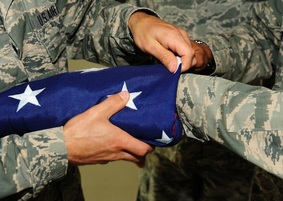 Airmen from the 319th Air Base Wing practice folding the flag before a formal retreat ceremony August 19, 2015, on Grand Forks Air Force Base, North Dakota. Squadrons take turns performing a formal retreat ceremony each week during the spring and summer months. (U.S. Air Force photo by Airman 1st Class Ryan Sparks/Released)
