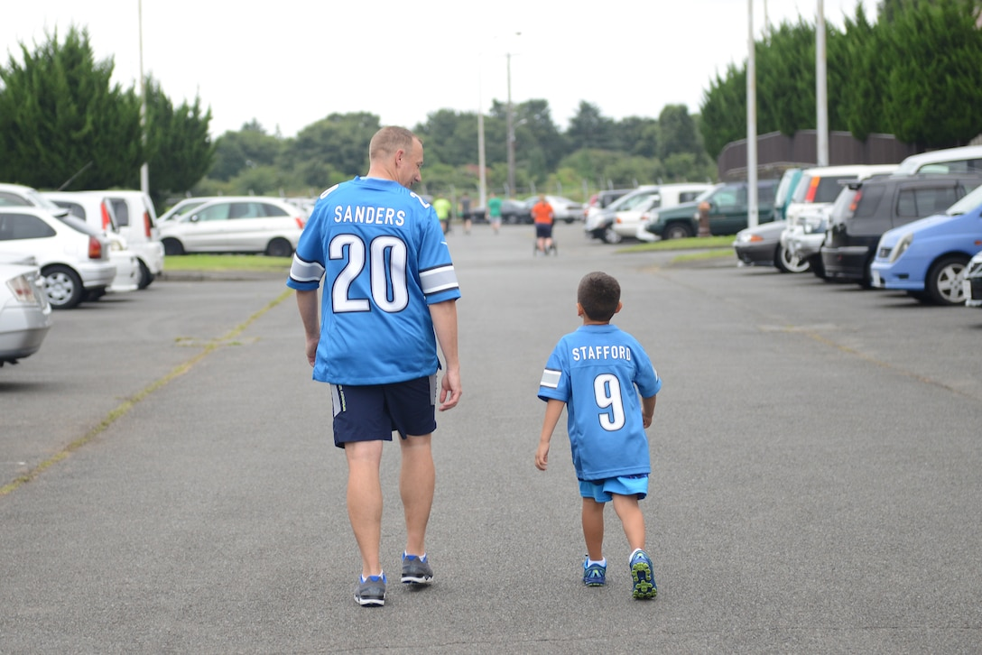 A father and son wear matching Detroit Lions football jerseys after the 'Football Frenzy 5K' at Yokota Air Base, Japan, Aug. 28, 2015. Participants wore jerseys supporting their favorite football teams as part of the event. (U.S. Air Force photo by Senior Airman David C. Danford/Released)
