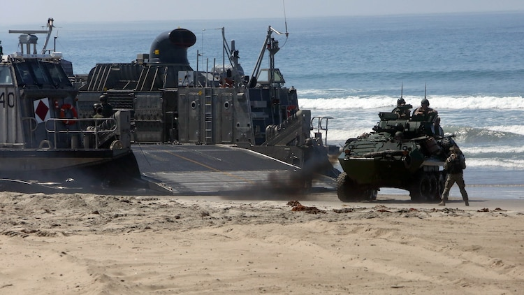 Marines with 3rd Light Armored Reconnaissance Battalion, 1st Marine Division, maneuver their light armored vehicles off Landing Craft Air Cushions (LCACs) from the Navy's Assault Craft Unit 5, during an amphibious raid demonstration in conjunction with a visit from the secretary of defense, aboard Marine Corps Base Camp Pendleton, Calif., Aug. 27, 2015. The LCACs transported the LAVs and Marines from the USS New Orleans (LDP 18) while Marines from Company A, 1st Battalion, 1st Marine Regiment, 1st Mar. Div. used amphibious assault vehicles with 3rd Assault Amphibian Battalion, 1st Mar. Div. to assault their objective.