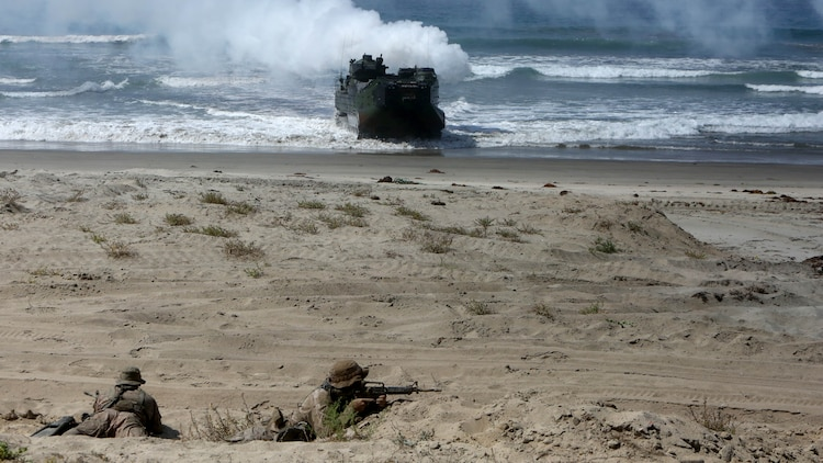 Marines with 1st Reconnaissance Battalion, 1st Marine Division, reconnoiter the beach as Company A, 3rd Assault Amphibian Battalion, 1st Mar. Div., maneuvers ashore during an amphibious raid demonstration in conjunction with a visit from the secretary of defense, aboard Marine Corps Base Camp Pendleton, Calif., Aug. 27, 2015.   The amphibious assault vehicles transported infantrymen with Company A, 1st Battalion, 1st Marine Regiment, 1st Mar. Div. to shore after disembarking the amphibious transport dock ship USS New Orleans (LPD 18) while 3rd Light Armored Reconnaissance Battalion, 1st Mar. Div., provided additional security.
