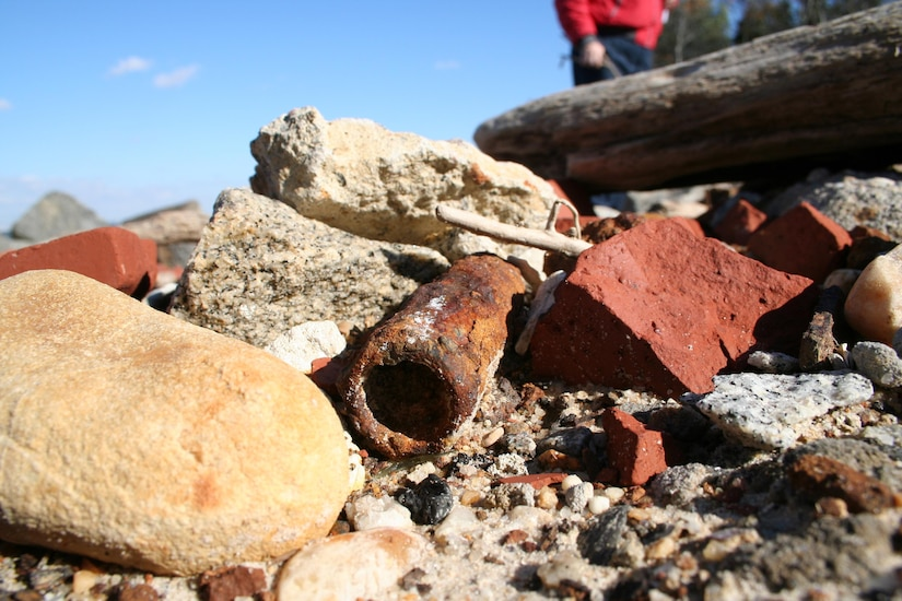 SUFFOLK, Va. -- A piece of ordnance lays among rocks on the beach at the Former Nansemond Ordnance Depot Dec. 2, 2005. In 1987 the Former Nansemond Ordnance Depot  became a matter of public concern when a piece of crystalline TNT was found at the Tidewater Community College, Portsmouth Campus. Extensive historical research, investigations, and testing led the U.S. Environmental Protection Agency to place this site on the National Priority list in 1999. The U.S. Army Corps of Engineers has managed the clean-up project on this site since. (U.S. Army photo/Patrick Bloodgood)