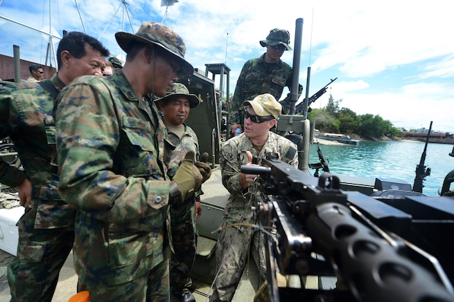 U.S. Navy Petty Officer 2nd Class Andrew Baldwin demonstrates firing a .50-caliber machine gun to members of the Thai navy's Riverine Patrol Regiment during Cooperation Afloat Readiness and Training Thailand 2015 in Sattahip, Thailand, Aug. 27, 2015. In its 21st year, the exercise includes the U.S. Navy, U.S. Marine Corps and the armed forces of nine partner nations. U.S. Navy photo by Petty Officer 1st Class Joshua Scott