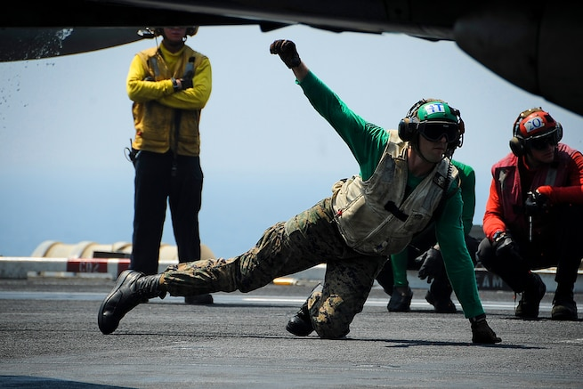 A U.S. seaman gives the OK to launch an F/A-18C Hornet from the flight deck of the aircraft carrier USS Theodore Roosevelt in the Arabian Gulf, Aug. 27, 2015. The Hornet is assigned to Marine Strike Fighter Squadron 251. The carrier is in the U.S. 5th Fleet area of operations supporting Operation Inherent Resolve, which include strike operations in Iraq and Syria as directed. U.S. Navy photo by Petty Officer 3rd Class Anna Van Nuys