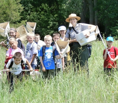 Rock Island District Park Ranger, Tracy Spry, stands with some students attending a Jr. Ranger program at Lake Red Rock in 2014.