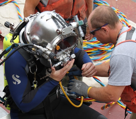 District dive team member, Mark Hoewing (right),shifthead at Lock and Dam 20,helps Nathan Gorham, assistant lockmaster at Locks and Dam 15, with securing his dive helmet in preparation for a dive at Locks and Dam 15.