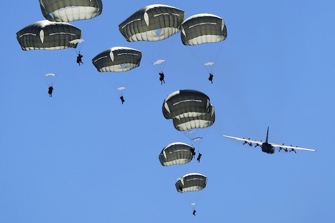 U.S. paratroopers descend after jumping from a C-130 Hercules over a drop zone on Joint Base Elmendorf-Richardson, Alaska, Aug. 24, 2015. U.S. and Japanese paratroopers used U.S. and Australian aircraft during the practice jump as part of Pacific Airlift Rally 2015, a biennial tactical exercise. The U.S. paratroopers are assigned to 1st Battalion , 501st Infantry Regiment, and the Hercules is assigned to the 374th Wing from Yokota Air Base, Japan. U.S. Air Force photo by Alejandro Pena