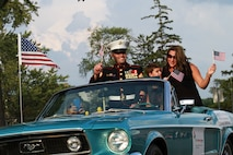 "U.S. Marine Corps Gunnery Sgt. Dominic Freda, cruises down Woodward Avenue with his wife Lindsay and son Dominic ""duce"" II, during the annual Woodward Dream Cruise in Royal Oak, Michigan Aug. 14, 2015. Freda, the staff noncommissioned officer in charge of Recruiting Sub-Station Madison Heights, was recognized as the cruises grand marshal and led the first line of automobiles down the avenue.   (U.S. Marine Corps photo by Sgt. Joshua Heins/Released)"