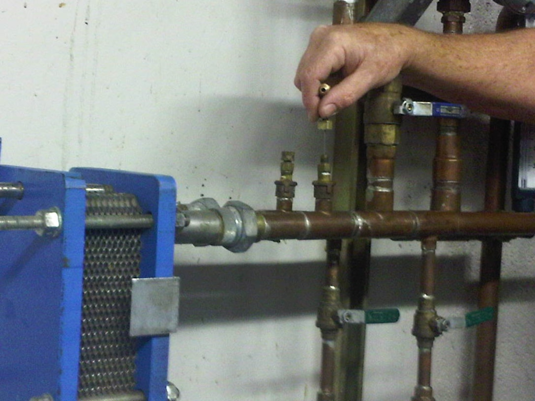 Testing and balancing technician set-up to measure flow rate and temperature of the fluid. This typically occurs during the construction phase of the commissioning process.