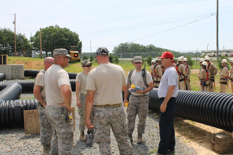 """U.S. Air Force Staff Sgt. Jeret Kinnaird, firefighter for the North Carolina Air National Guard, 145th Civil Engineer Squadron, explains to visiting airmen from the Oklahoma Air National Guard, the importance of the Confined Space Trainer, as students prepare to repel during a Rescue Technician I class held at the 145th Regional Training Site, New London, N.C., June 23, 2015. Kinnaird, an instructor for ANG Rescue Technician Course, received the """"Chief Albert Fitzpatrick Award"""" for Firefighter of the Year, July 22, 2015. (U.S. Air National Guard photo by Master Sgt. Patricia F. Moran, 145th Public Affairs/Released)"""