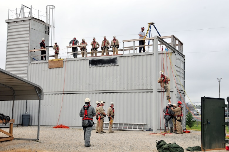 """U.S. Air Force Staff Sgt. Jeret Kinnaird, firefighter for the North Carolina Air National Guard, 145th Civil Engineer Squadron, observes from rooftop as military firefighters participate in training for certification including high angle basket raising & lowering and ground ascending, descending & passing a knot at the 145th Civil Engineer Regional Training Site, New London, N.C. Kinnaird, an instructor for ANG Urban Search and Rescue Technician I and II Courses, was presented the """"Chief Albert Fitzpatrick Award"""" for Firefighter of the Year, July 22, 2015. (U.S. Air National Guard photo by Master Sgt. Patricia F. Moran, 145th Public Affairs/Released)"""