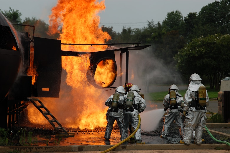 """U.S. Air Force Staff Sgt. Jeret Kinnaird, firefighter for the North Carolina Air National Guard, 145th Civil Engineer Squadron, gives instructions to other firefighters as they extinguish a fire on the wing of a simulated aircraft during Aircraft Rescue Fire Fighting Burns training held at the North Carolina Air National Guard Base, Charlotte Douglas International Airport. Kinnaird, who on July 22, 2015, was presented with the """"Chief Albert Fitzpatrick Award"""" for Firefighter of the Year for 2014, is an instructor for ANG Rescue Technician I and II Courses. (U.S. Air National Guard photo by Staff Sgt. Pamela Robbins, 145th Public Affairs/Released)"""