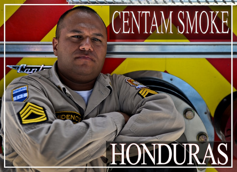 """Alix Arnaldo Ramirez Midence, a volunteer firefighter for 16 years, stops for a photo opportunity during the CENTAM SMOKE exercise Aug. 28, 2015, at Soto Cano Air Base, Honduras. The exercise, known as Central America Sharing Mutual Operational Knowledge and Experience, or """"CENTAM SMOKE,"""" brings together U.S. and Central American firefighters to train and improve their ability to work together. (U.S. Air Force illustration by Staff Sgt. Jessica Condit)"""