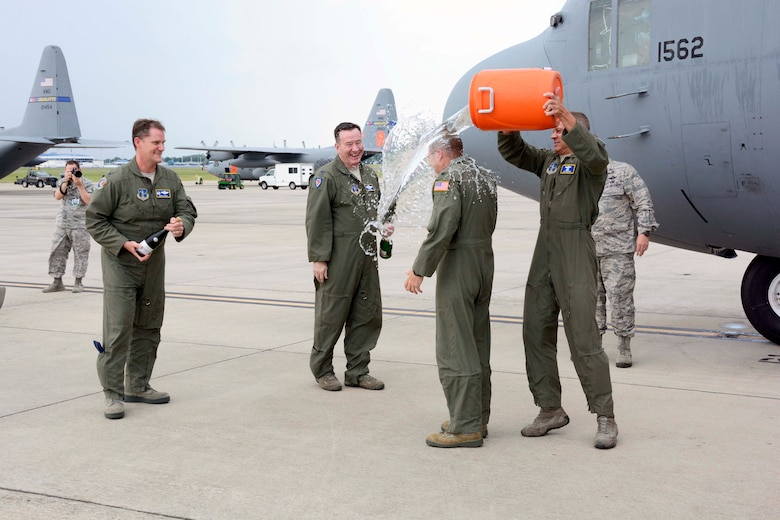 """In a tradition nearly as old as military aviation itself, U.S. Air Force Col. Charles D. Davis III, gets doused with a bucket of ice water by Lt. Col. James Pearson, Chief of Current Operations, 145th Operations Support Squadron, following his """"fini"""" flight, at the North Carolina Air National Guard Base, Charlotte Douglas International Airport, July 28, 2015, symbolizing the end of 38 years of honorable military service. (U.S. Air National Guard photo by Master Sgt. Patricia F. Moran, 145th Public Affairs/Released)"""