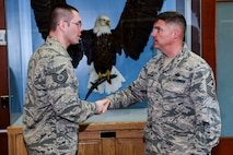 Tech. Sgt. Nicholas Rau, 460th Space Wing Public Affairs NCOIC of community engagement, left, receives a coin from Chief Master Sgt. Patrick McMahon, Air Force Space Command command chief, Aug. 28, 2015, at the 460th SW Headquarters Building on Buckley Air Force Base, Colo. McMahon visited Buckley AFB for the first time after becoming the senior enlisted leader of Air Force Space Command, communicating his goals, answering Airman's questions and recognizing outstanding performers. (U.S. Air Force photo by Senior Airman Phillip Houk/Released)