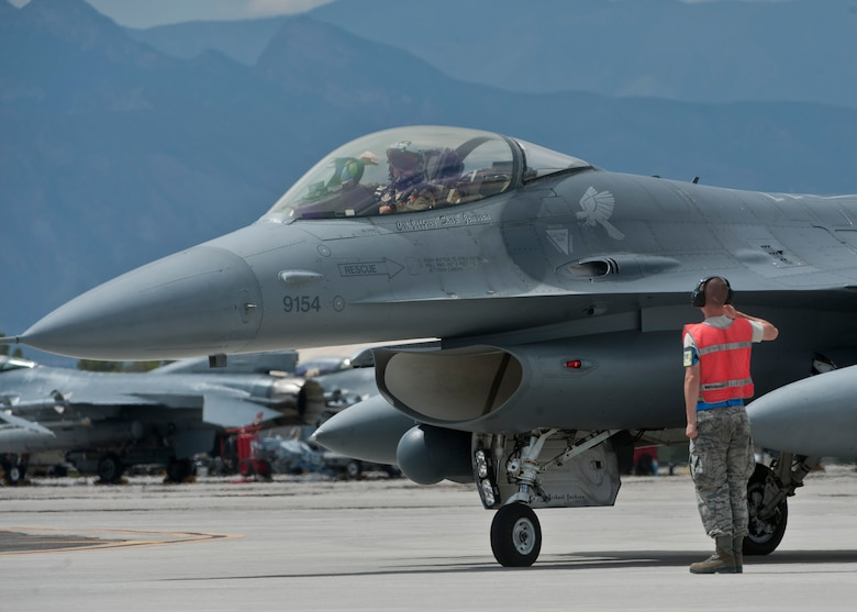 An F-16 Fighting Falcon pilot assigned to the 311th Fighter Squadron, Holloman Air Force Base N.M., salutes a crew chief before taking off as part on an exercise during Red Flag 15-4 at Nellis Air Force Base, Nev., Aug. 27, 2015. Red Flag involves a series of intense air-to-air combat exercises designed to prepare U.S. and allied forces for future real world conflicts. (U.S. Air Force photo by Airman 1st Class Jake Carter)