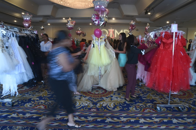 Women scramble to find dresses to try on during the USO sponsored Operation That's My Dress event in Las Vegas, Aug. 30, 2015. More than 1500 dresses in multiple sizes- valued between $400 and $1200- were donated to over 800 active duty females, spouses, and teenage daughters as a thank you for their service and sacrifice. (U.S. Air Force photo by Tech. Sgt. Nadine Barclay)