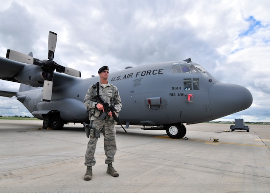 Staff Sgt. Matthew Higgins, 914th Security Forces Squadron member stands guard over a C-130 H2 aircraft at the Niagara Falls Air Reserve Station, N.Y.  on August 27, 2015. Higgins is one of many security forces personnel that maintain security on the flight line and help protect Air Force assets 24 hours a day 365 days a year.  (U. S. Air Force photo by Peter Borys)