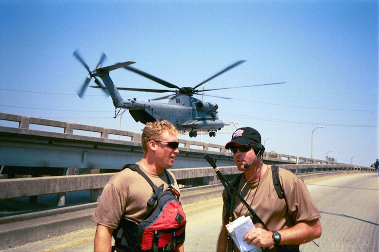 Two Kentucky Air National Guard Special Tactics troops confer as an Air Force MH-53 helicopter lands on Interstate 610 to evacuate New Orleans residents following Hurricane Katrina Sept. 4, 2005. (U.S. Air National Guard photo)