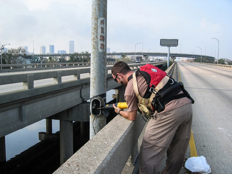 A special tactics troop from the Kentucky Air National Guard cuts down street light poles along Interstate 610 in New Orleans following Hurricane Katrina Sept. 3, 2005, to clear the way for a helicopter landing zone. (U.S. Air National Guard photo)