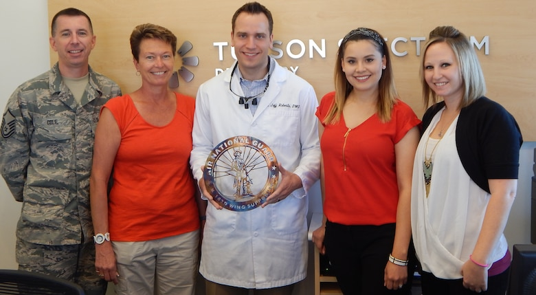 Barb Gavre and Master Sgt. Michael Cole present Dr. Jeffery Roberts and his staff from Tucson Spectrum Dentistry with the 162nd Family Readiness Support Award on August 27, 2015. Roberts provided free dental services to members of the 162nd Wing.
