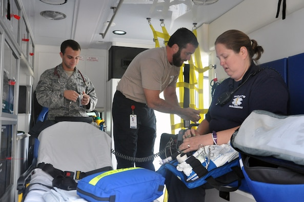 Wright Patterson AFB Medical Center Paramedics Senior Airman Jacob Miller, Kevin Bull, and Amy Wilt inspect equipment and supplies on one of the medical center's five ambulances to ensure they are ready to respond to emergencies anywhere on base. Air Force photo by Bryan Ripple.