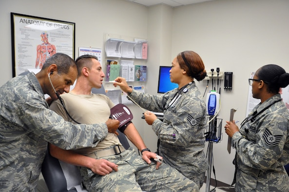 Senior Airman Michael Lizzi, a medical technician with the Family Health Flight, undergoes a portion of his annual Physical Health Assessment (PHA) August 20. Performing the assessment are Dr. (Lt. Col). Reynold D'Lima, Physician Element Chief; Staff Sgt. Tinesha Oliver, Family Health Clinic Supervisor; and Tech. Sgt. Susan Rhodes, NCOIC, Family Health Red Element. Air Force photo by Bryan Ripple.