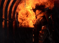 Staff Sgt. Michael White, 51st Civil Engineer Squadron crew chief, stands amid the flames of a training fire Aug 26, 2015, at Osan Air Base, Republic of Korea. White was training members of the Songtan fire station on proper aircraft fire extinguishing techniques and procedures. (U. S. Air Force photo by Staff Sgt. Benjamin Sutton)