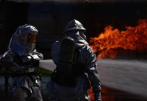 Firefighters from the Songtan fire station perform fire-sweeping maneuvers during a training event Aug 26, 2015, at Osan Air Base, Republic of Korea. After the initial fire is out, the firefighters continue to spray the burn site until all the hot spots were gone and all the flames were out. This process, known as overhaul, is used to ensure the fire won't start back up. (U. S. Air Force photo by Staff Sgt. Benjamin Sutton)