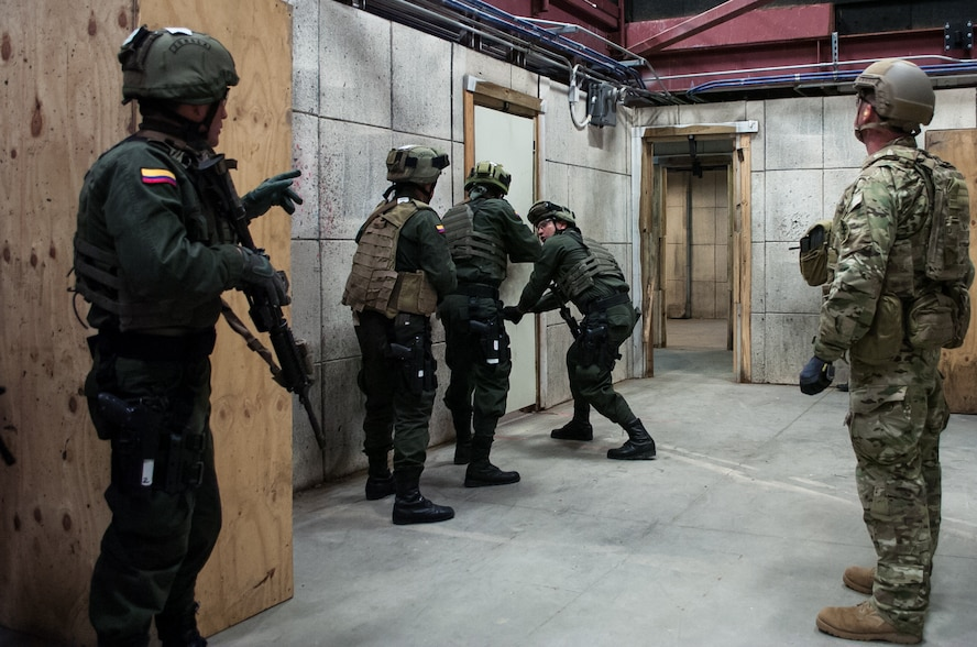 A U.S. Army Green Beret right, observes members of the Colombian Compañía Jungla Antinarcóticos simulate emplacing an explosive door-breaching charge inside a shoot house during a joint training exercise on Eglin Air Force Base, Fla., Nov. 20, 2015. The Green Beret is assigned to the 7th Special Forces Group. U.S. Army photo by Maj. Thomas Cieslak