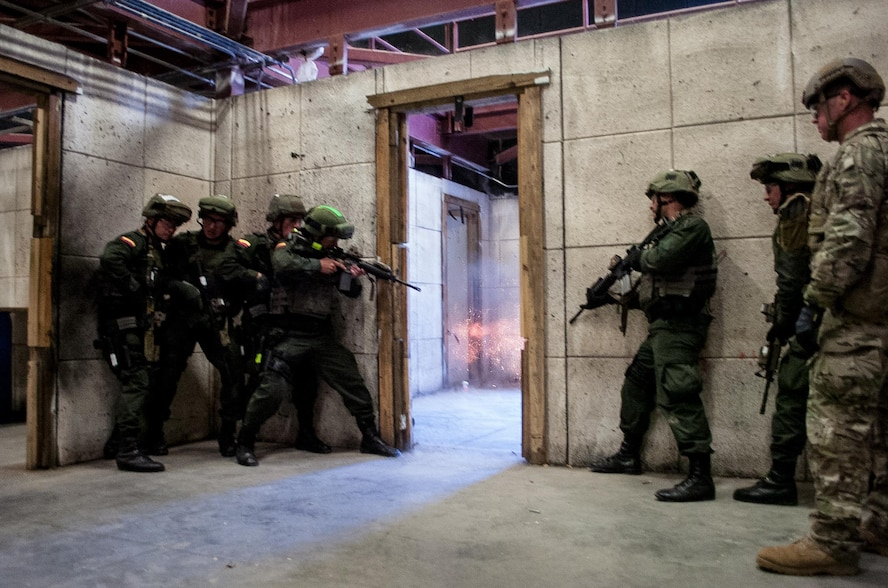 An explosive door-breaching charge detonates during a live-fire exercise as members of the Colombian Compañía Jungla Antinarcóticos assault a doorway inside an Eglin Air Force base shoot house on November 20, 2015.
