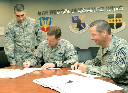 Col. Douglas Lee (center), 9th Reconnaissance Wing commander, and Command Chief Master Sgt. Randy Kwiatkowski (right), 9 RW command chief, sign their Combined Federal Campaign donations Dec. 1, 2015. The CFC is the only authorized solicitation of Federal employees in the workplace on behalf of charitable organizations. (U.S. Air Force photo by Robert Scott)