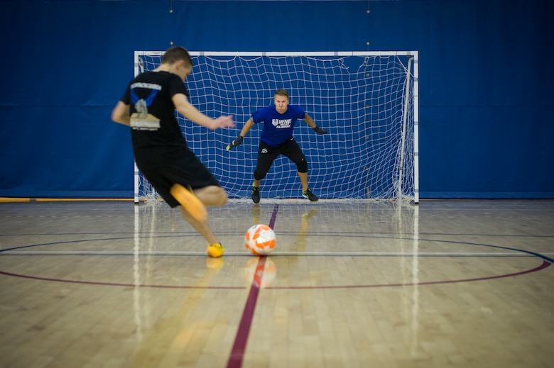 An Airman from the 5th Contracting Squadron takes a penalty kick during the intramural indoor soccer championship at Minot Air Force Base, N.D., Nov. 24, 2015. After coming down to penalty kicks, 5th CONS beat the 5th Medical Group team. (U.S. Air Force photo/Senior Airman Apryl Hall)