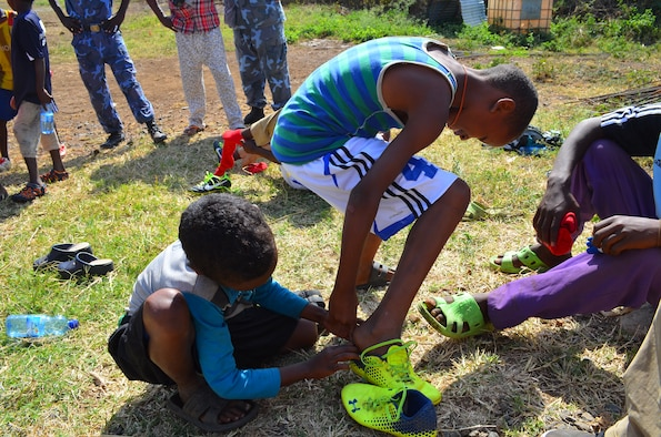 Two Ethiopian children help each other try on their new soccer shoes Aug. 21, 2015, at Arba Minch, Ethiopia. Brayden Tester, son of Chief Master Sgt. David Tester, U.S. Air Forces in Europe operations superintendent, spearheaded a donation drive in April 2015 that resulted in the collection of more than 100 different cleats, soccer balls and jerseys that were then donated to children in Ethiopia. (Courtesy photo)