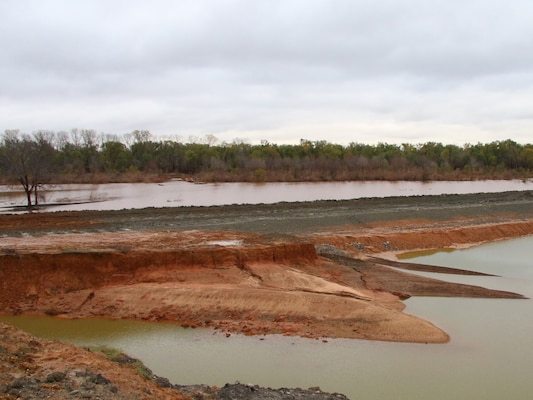 "The temporary cofferdam at the Cumberland Levee repair site has been reinforced with a 36"" windrow to keep water from overtopping the structure after several days of rain once again brought water levels out of the banks of the Washita River near the construction site Nov. 30, 2015. The dam was built for events such as this in order to keep the site free of excess water during high-water events. The Cumberland Levee repair site is in Phase I of a repair project by the Tulsa District, U.S. Army Corps of Engineers, after breaching earlier in 2015 due to record amounts of rainfall. (Photo by Preston Chasteen/Released)"